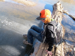 Dalan is sitting on the log to test the ice thickness.  He broke off a piece shortly after this was taken