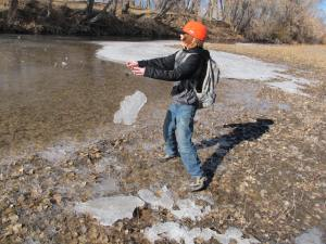 Throwing hunks of ice onto the icy area that looks like just plain water