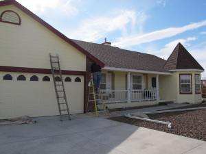 Painting the trim on the front of the house.