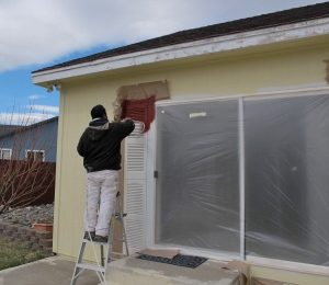 Charlo is spraying the back door fake shutters.