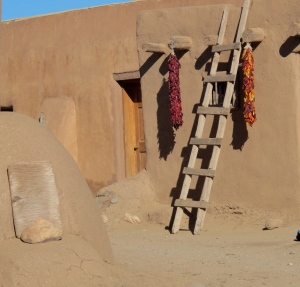 The red and multicolored things hanging down are called ristras. The red one is made up on red chiles while the other one is basically ornamental with multi-colored corn ears. The pueblo people used the corn mostly while the chiles were grown in the southern part of the state.