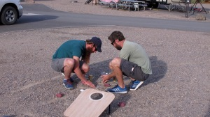 Another game we played was Cornhole…tossing beanbags to a board with a hole in it. This is Jason and Scott putting the beans (gravel?) back into the bags when the seams ripped.
